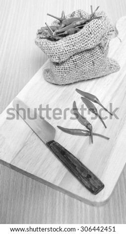 red chili peppers on cutting board over wood table background black and white tone color style