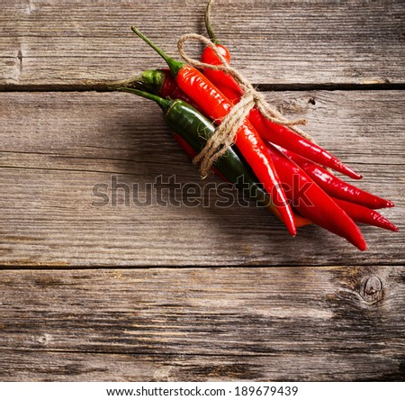 red chili peppers on old wooden table - stock photo