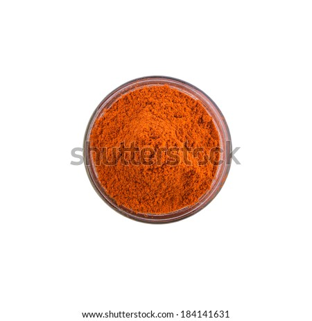 Red chili powder in glass container over white background