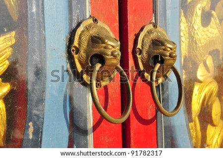 Red chinese dirty door with a lion dragon head - stock photo