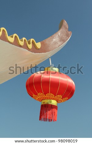 Red Chinese Lantern hanging on edge of concrete roof against blue sky - stock photo