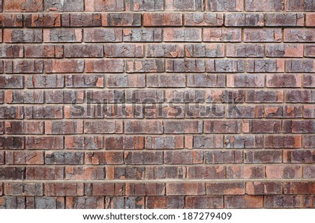 Red Chipped old brick wall with two rows protruding - stock photo