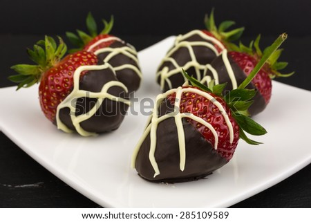 red chocolate dipped in dark chocolate decorated with white chocolate drizzle - stock photo