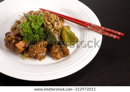 Red chopsticks on plate of General Tso's chicken - stock photo