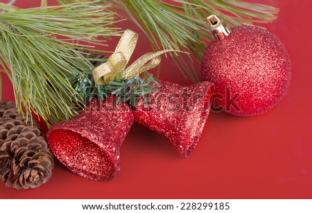 Red Christmas ball and bells with pine needles and cone on red background - stock photo