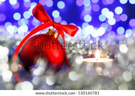 Red christmas ball and candle, blured purple lights at the background