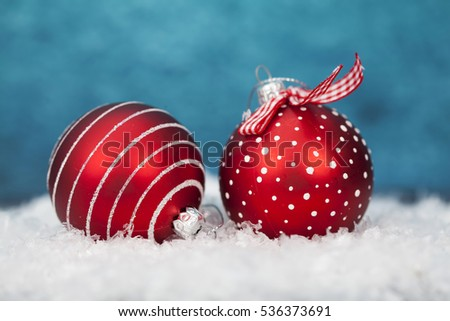 Red Christmas ball and decoration on blue background in the snow. Magic holiday lights. Merry Christmas and a Happy New Year