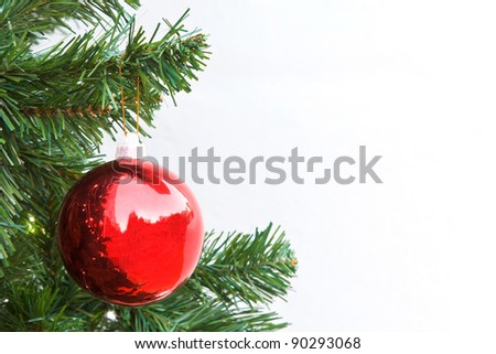 Red Christmas ball and green spruce branch on white background - stock photo