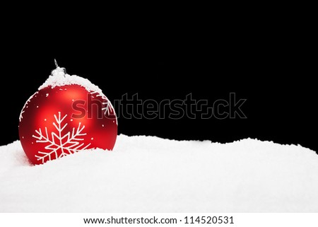 red christmas ball in snow with black background - stock photo