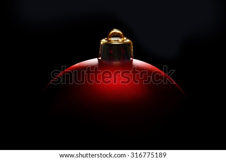 red Christmas ball in tense light on black background - stock photo