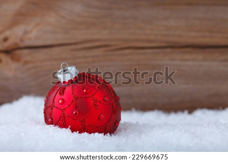 red christmas ball inside of snow - stock photo