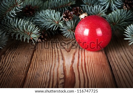 Red christmas ball on wooden background with branches of silver spruce. Copy space - stock photo