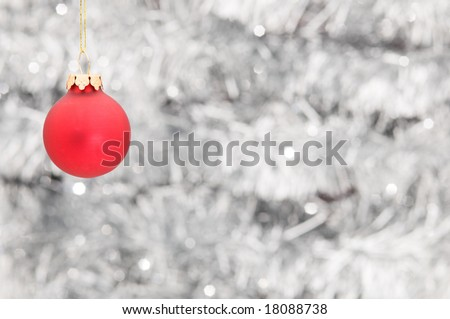 Red Christmas ball ornament hanging over shiny silver garland background, focus on ball