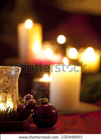 Red christmas ball ornaments with burning candles in the background (shallow depth of field)