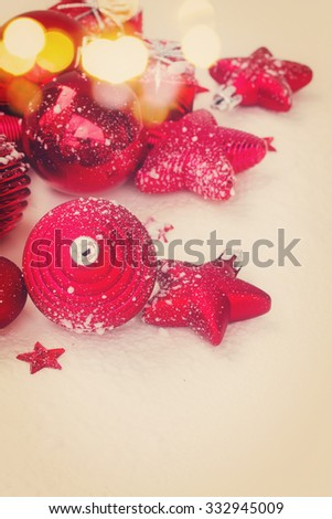 red  christmas balls and stars on snow background, retro toned
