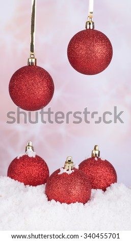 Red Christmas balls hanging and in snow against a colorful background - stock photo