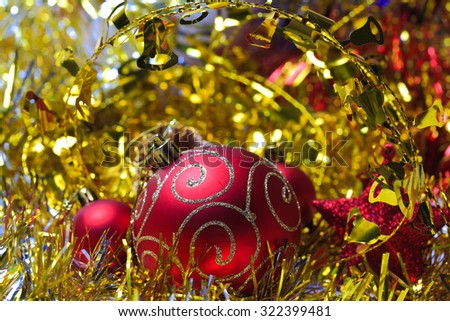 Red christmas balls in the golden tinsel defocused backgrounds - stock photo