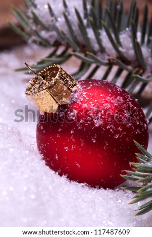 red christmas balls lying on snow under a pine tree - stock photo