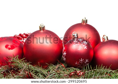 red Christmas balls on green spruce branch isolated on white background - stock photo