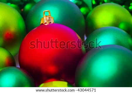 Red christmas bauble amongst green baubles