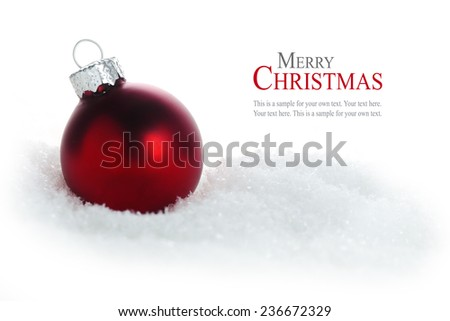 red christmas bauble in snow isolated on white background, sample text in the copy space, close up - stock photo