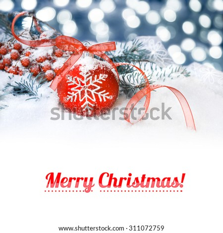 """Red Christmas bauble on a neutral winter background, caption """"Merry Christmas"""" on flat white background. You can exchange it for your text if you wish. - stock photo"""
