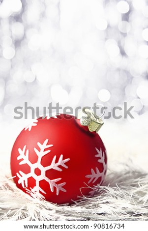 red christmas bauble with snowflake and bokeh - stock photo
