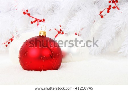 Red christmas bauble with white christmas balls and white tree in the  background