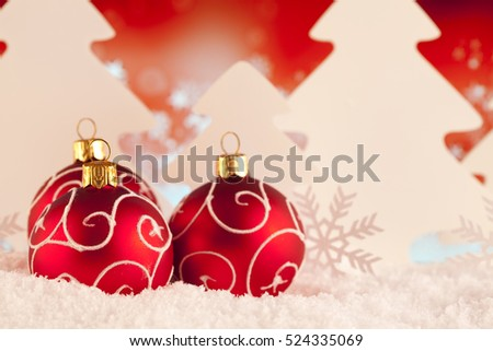 Red Christmas baubles and trees on snow