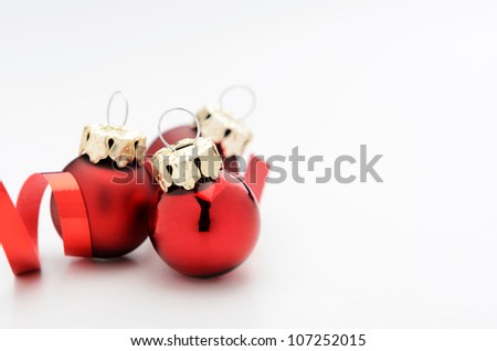 Red christmas baubles decoration with ribbon isolated on white - stock photo