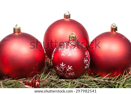 red Christmas baubles on green spruce tree branch isolated on white background - stock photo