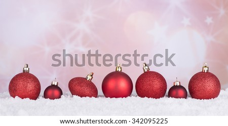Red Christmas baubles on snow with holiday background - stock photo