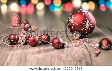 Red Christmas baubles on twisted red-white cord on wooden table - stock photo