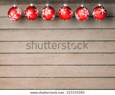 Red christmas baubles with white stars on wooden background - stock photo