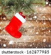 Red christmas boot with gifts on background wooden wall - stock photo