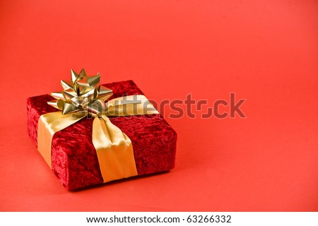 Red Christmas Box Tied In Ribbon On A Red Background