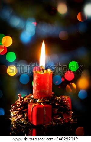 Red christmas candle in atmospheric light with gift