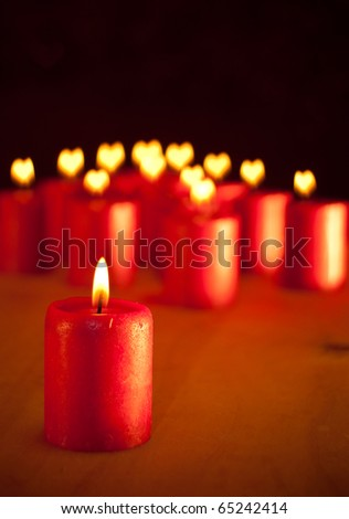 Red Christmas candle on table - with group of similar candles with hearts for flames on background