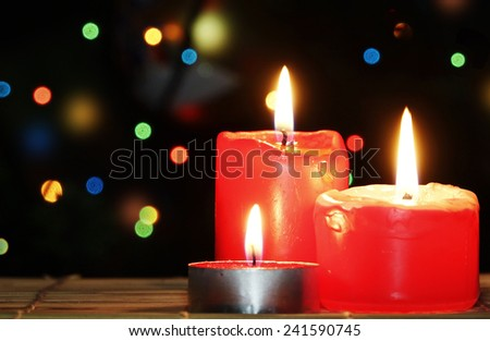 Red Christmas Candles burn against Christmas Tree with Garland Lights                     - stock photo