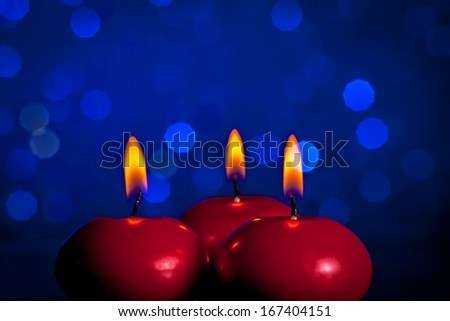 red christmas candles on blue bokeh background with space for text
