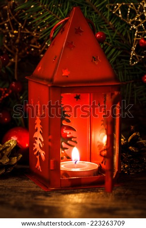 Red christmas candlestick over holiday decorations on the table - stock photo