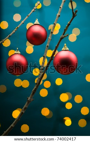 Red Christmas decoration in front of lights on tree branch - stock photo