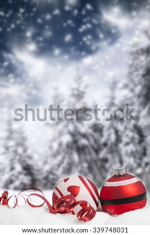 Red Christmas decorations in the snow, snow cowered pine trees in the background - stock photo