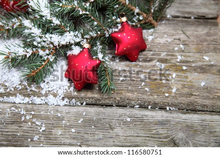 Red Christmas decorations on spruce branches with snow