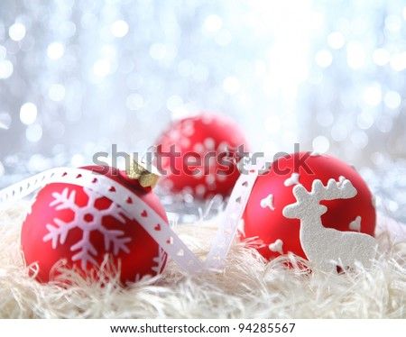 Red Christmas decorations on white material with a sparkling bokeh of silvery festive lights - stock photo