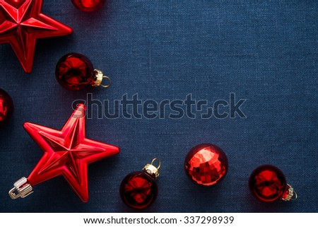 Red christmas decorations (stars and balls) on dark blue canvas background. Merry xmas card. Winter holiday theme. Space for text. Happy New Year. - stock photo