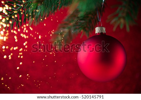red christmas decorative ball on the xmas tree on glitter bokeh background with twinkle lights