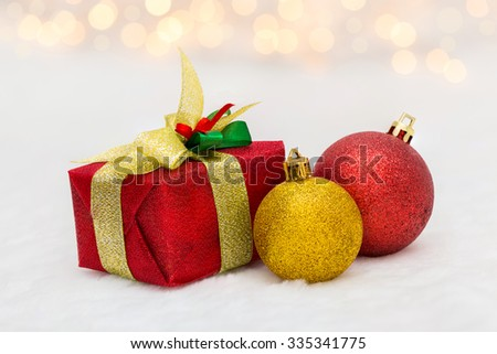 Red Christmas gift box with shiny golden ball. Bokeh with glow effect on white background. - stock photo
