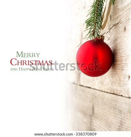 Red Christmas hanging on a wooden wall, background faded to white, copy space with sample text Merry Christmas and Happy New Year - stock photo