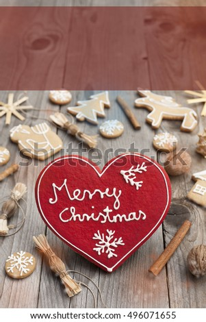 Red Christmas heart shaped gingerbread on wooden background. Space left for copy. Perfect for greeting cards. Merry Christmas written with icing in English